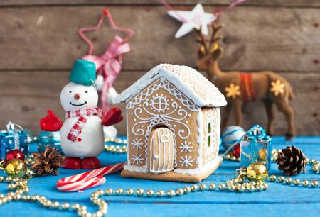 Homemade gingerbread house with candy windows on a blue wooden table with Christmas decorations. Selective focus and space for text. 版權商用圖片