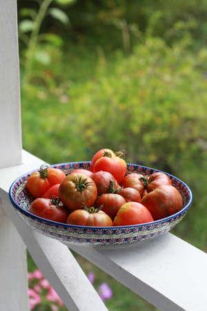 Ripe tomatoes in a ceramic dish on the veranda railing