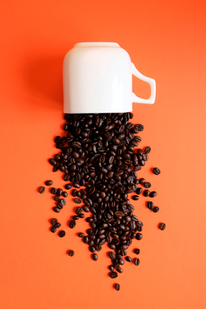 Coffee beans in coffee cup upsidedown on Living Coral background. Color of the year 2019 concept. Vertical layout Stock Photo