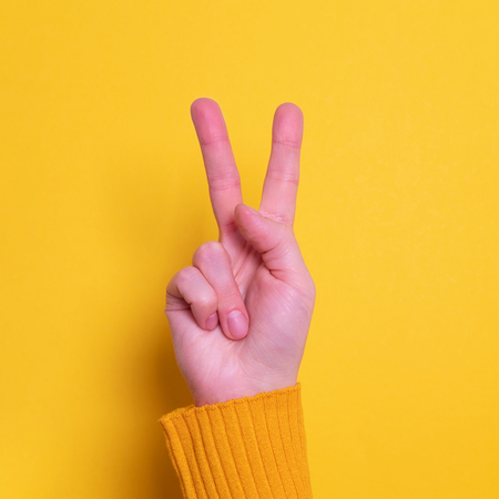 Beautiful woman hand making victory sign gesture on yellow bright background Banco de Imagens
