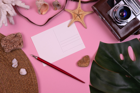 Womens traveler accessories: coral, shell, starfish, straw hat, tropical leaf monstera, retro camera, postcard with copy space, pen on pink background. Summer concept of travel background Reklamní fotografie - 124995074