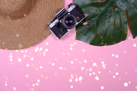 Womens traveler accessories: straw hat, tropical leaf monstera, retro camera on pink background with bokeh lights. Concept of travel with copy space. Summer background. Flat lay, overview