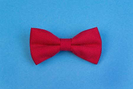 Rote Fliege auf blauem Hintergrund. Glückliches Vatertagskonzept. Minimalistisches Design Standard-Bild