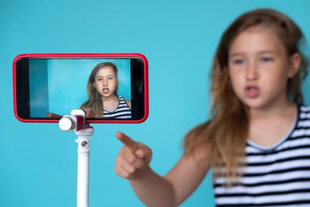 Girl posing in front of phone camera for selfie. Focus o smartphone screen fixed on tripod. Recording homemade video. Happy smiling child. Cute kid pointing up. Simple wallpaper, background