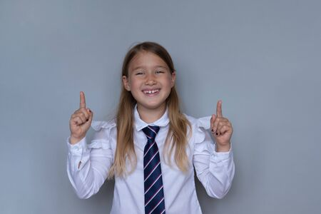 Young schoolchild pointing up portrait. Preteen schoolgirl looking at camera, gesturing at ceiling. Happy girl, kid in school uniform. Back to school, joyful, cheerful pupil, student ready for class Stock Photo