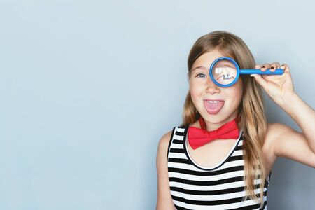 Young girl giving looking through magnifying glass portrait on grey background. Young scientist, exploring with magnifier, loupe. Happy, adorable kid in red bowtie and striped dress showing tongue