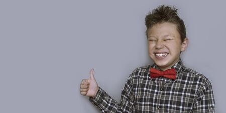 Young boy giving thumbs up portrait on violet background. Child enjoying, approving of something. Happy kid in red bowtie and checkered shirt giving likes. Fun, cheerful pastime, activity for children