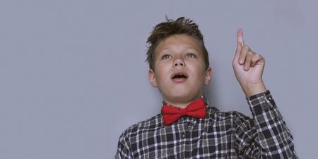 Young schoolchild pointing up portrait. Preteen schoolboy gesturing at ceiling. Happy boy, kid incheckered shirt with red bow tie. Back to school, cheerful pupil. I have an idea and insight concept 写真素材