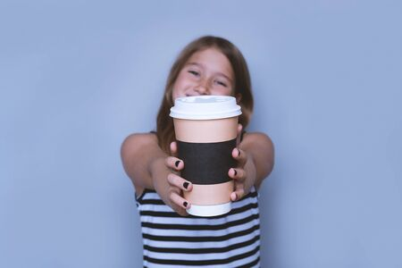 Smiling girl giving, showing coffeecup closeup side view. Drinking hot, energizing coffee to go, take away drink in disposable paper cup . Everyday routine with your child. Safe, recyclable materials 写真素材