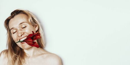 Portrait 40 years old woman with blond hair and red lily flower in mouth on light gray background with copyspace