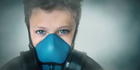 Young boy wearing gasmask, respirator portrait. Effects of worldwide air pollution, industrial influence on environment. Protection from dangerous air particles, gas, smog, transmitted diseases