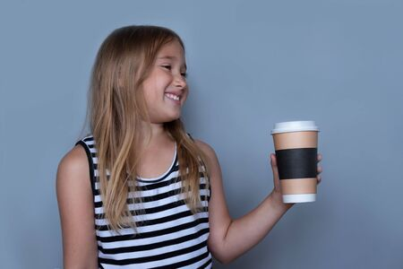 Smiling girl giving, showing coffeecup closeup side view. Drinking hot, energizing coffee to go, take away drink in disposable paper cup . Everyday routine with your child. Safe, recyclable materials Banco de Imagens