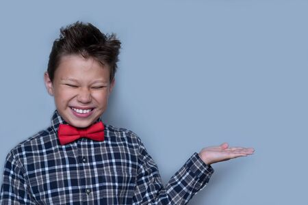 Small boy showing something with palm of hand. Nerdy schoolboy presenting school project portrait. Schoolboy with white smile, preteen child with cupped hand on grey background. Dentistry concept