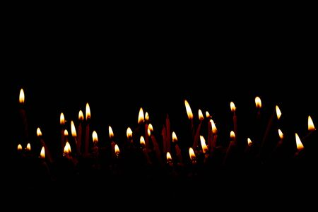 Candle burning brightly on black background. Happy birthday concept