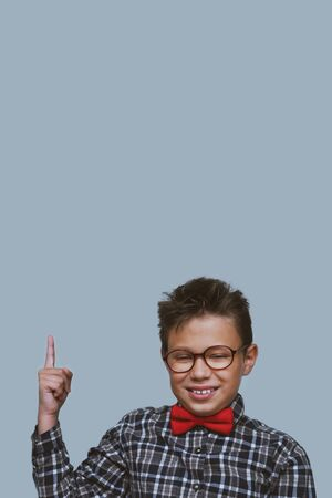 Young schoolchild pointing up portrait. Preteen schoolboy with glasses, gesturing at ceiling. Happy boy, kid in checkered shirt. Back to school, joyful, cheerful pupil, dentistry concept