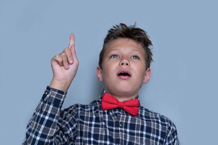Young schoolchild pointing up portrait. Preteen schoolboy gesturing at ceiling. Happy boy, kid incheckered shirt with red bow tie. Back to school, cheerful pupil. I have an idea and insight concept Banco de Imagens