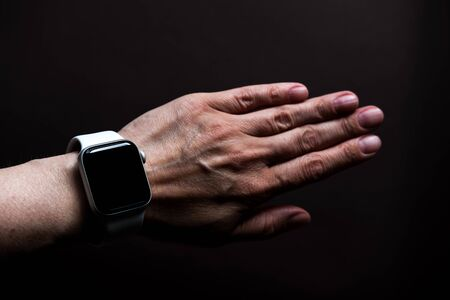 Chekhov, Russia - July 19, 2019: Apple Watch Series 4 white color with hand. A new watch from an Apple company closeup isolated on dark background Editorial