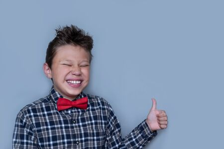 Young boy giving thumbs up portrait on violet background. Child enjoying, approving of something. Happy kid in red bowtie and checkered shirt giving likes. Fun, cheerful pastime, Dentistry concept