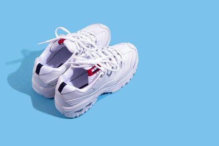Pair of white sneakers on blue background with copyspace. Sport running concept