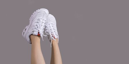 Girl in stylish white sneakers on gray background closeup with copyspace Banco de Imagens