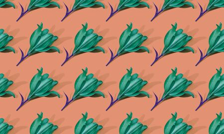 Seamless pattern of green lilies on orange background trend flat lay concept with fashionable toning. Many flowers pattern Banco de Imagens