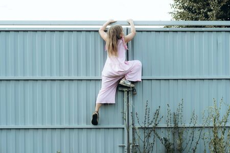 Girl climbing metal fence outdoor. Curious child on high white painted gates. Naughty kid playing outside, breaking rules. Childhood and youth concept. Restless teen entering private property