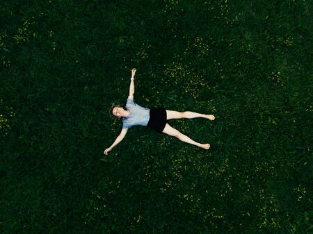 40 years old woman with arms and legs outstretched lying and similing on green grass in park meadow. Beautiful summertime. Hello summer and sport consept Banco de Imagens