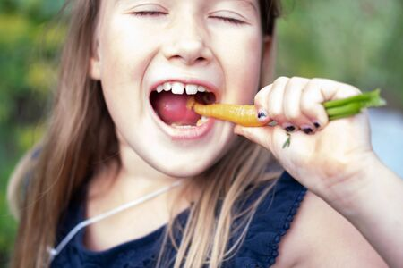Girl eating carrot. Child face closeup. Healthy, organic food. Fresh ripe vegetable. Summertime, spring sweet treat. Eco quick snack. Natural handpicked tasty food. Vegetarian and vegan diet Banco de Imagens