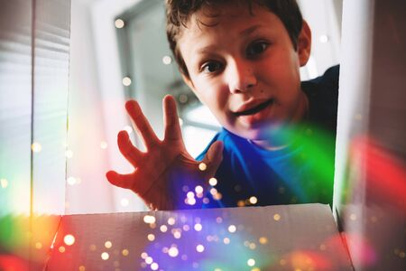 Happy boy unwrapping present. Child excited with Christmas holiday gift concept. Kid looking inside magic box with sparkles and rainbow bokeh lights effect. Teenager with getting birthday surprise Banco de Imagens