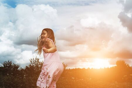 Happy girl rejoices summer. Young child playing outside. Summertime day activity. Happy, joyful kid outdoors. Having fun alone. Beautiful, scenic forest landscape. Picturesque scenery