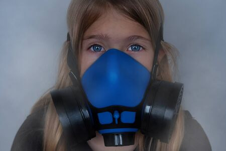 Young girl wearing gasmask, respirator portrait. Effects of worldwide air pollution, industrial influence on environment. Protection from dangerous air particles, gas, smog, transmitted diseases Archivio Fotografico