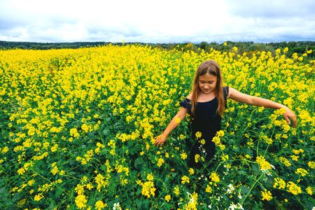 Happy girl rejoices summer walking on meadow with many yellow flowers. Young child playing outside. Summertime day activity. Happy, joyful kid outdoors. Having fun alone. Beautiful, scenic landscape