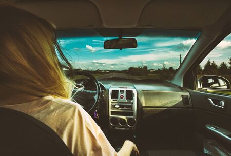 Blond young girl at wheel of car and looking at the road with beautuful countryside landscape. Woman driving.