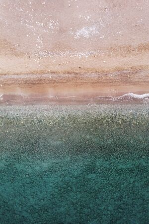 Aerial view of azure ocean and sandy beach. Beautiful seascape captured from drone. Tropical resort with clear transparent water background. Turquoise waves washing against sea shore