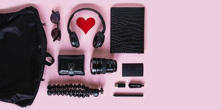 Trendy black accessories and contemporary gadgets on pink background, overhead view with copyspace. Modern headphones with heart symbol, camera lens, wallet, sunglasses, notebook and purse, flat lay