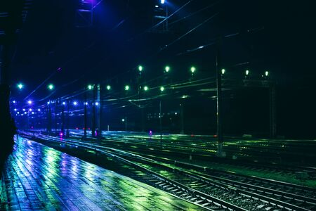 Railway station in rainy night with reflection. Beautiful background with night lights Banco de Imagens
