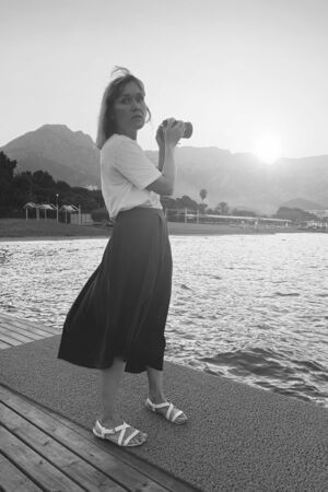 Beautiful woman with camera taking photos on beach with sea at sunset. Black and white background