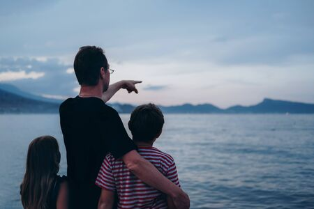 Father with son and daughter near river at sunset. Dad and kids watching sunrise together. Happy man and children relaxing on beach, family enjoying beautiful view. Bonding and togetherness