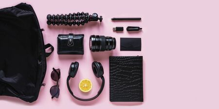 Modern black accessories, gadgets and lemon slice on pink background, top view. Flat lay composition with citrus fruit, headphones, notebook, flash drive, camera lens, sunglasses and bag