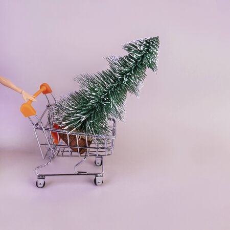 Trolley with fir tree on pink background. Holiday shopping, winter season sale metaphor. New year celebration, consumerism symbol. Toy pine in pushcart. Christmas backdrop with copyspace