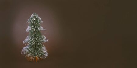 Toy fir tree on brown background. Evergreen spruce, botanical wintertime decoration with snow on green needles. Creative winter themed backdrop with copyspace. Christmas, new year celebration symbol