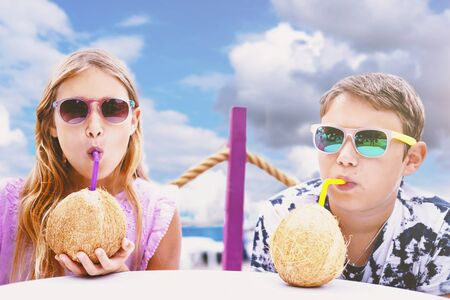 Children drinking coconut cocktails. Little girl and boy in sunglasses rest on tropical sea resort. Exotic summertime recreation, summer season holidays. Teenagers enjoying refreshing drinks