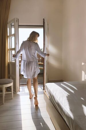 Beautiful young woman standing in doorway at sunset. Back view of sensual lady looking at sunny sky at daytime. Pretty girl enjoying morning sunlight. Female figure at door entrance in sunlit room