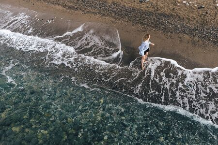 Aerial view of pretty woman walking along seashore. Beautiful girl on beach captured from drone. Tourist near ocean, enjoying waves. Summer vacation. Recreation and traveling concept