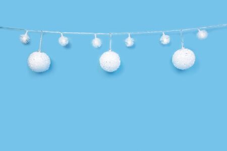 Christmas ornaments on cyan blue background. Festive decorations, white sparkling baubles and glowing lights garland. Traditional winter holiday celebration accessories. Xmas backdrop with copyspace