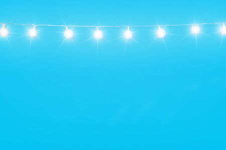 Christmas ornaments on cyan blue background. Festive decorations, white sparkling and glowing lights garland. Traditional winter holiday celebration accessories. Xmas backdrop with copyspace Stok Fotoğraf
