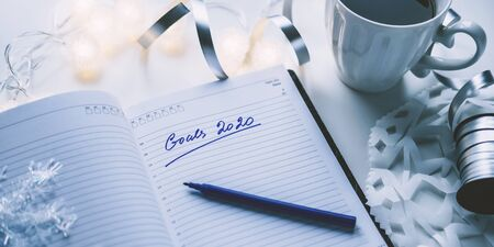 2020 goals written on a diary with light, hot coffe or tea and decoration. Happy New Year and motivation consept background