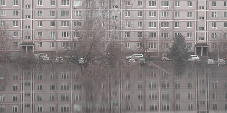Many windows on apartment house in small town with reflection. Gray dull background. Local lifestyle and architecture Stok Fotoğraf