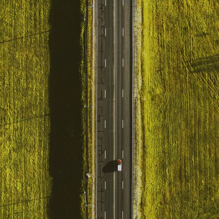 Drone view of moving red car on country side road with beautiful green field around