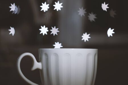 Cup of coffee or tea on table in cafe withwith bokeh lights from the window Stok Fotoğraf
